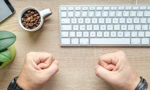 person-near-apple-keyboard-and-cup-with-coffee-beans-1419929